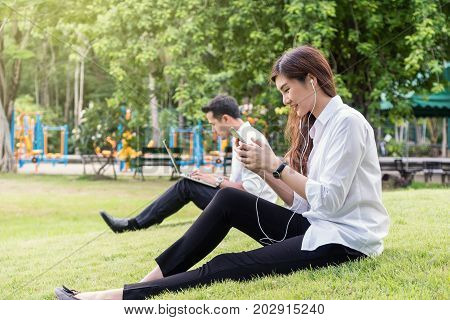 Happy asian couple listening the song via smart phone camera and using the laptop in the park lover and lifestyle concept