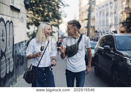 Attractive trendy hipster millennial couple or two friends walk on street in urban city they laugh and giggle make jokes and enjoy youth and life