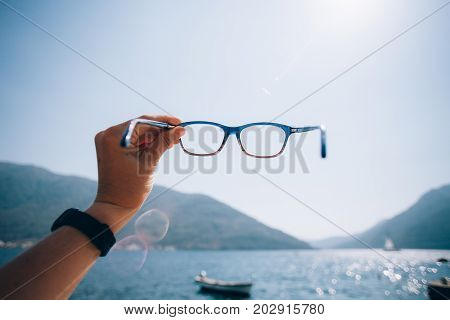 POV of female hand with black watch holding prescription glasses into sun or sky and through lenses you can see the crystal clear blue waters of touristic destination