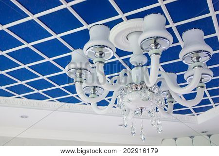 Glass chandelier on the ceiling. Stylish blue ceiling, divided into squares.