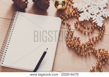 Christmas planning background. Prepare to winter holidays mockup. Closeup of xmas decorations, note papers and pen on wood. Copy space for wishlist or shedule
