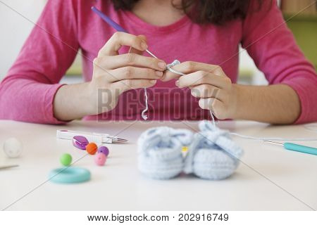 prenatal mother creating woolen bootees for her baby with a needle
