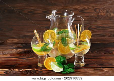 Close-up of a set of served fruity drinks on a light wooden background. Jar of a fruity cocktail and fancy glasses with decorative orange slices. Tropical citruses and mint for a refreshing beverage.