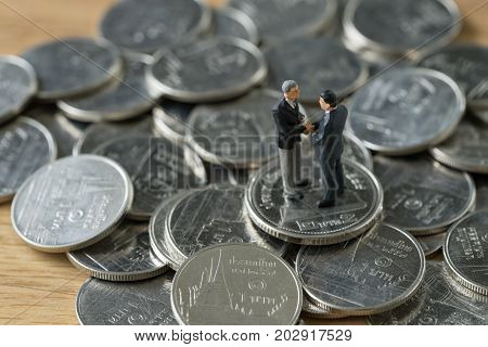 Miniature people: small figure businessmen handshaking on stack of coin as merger or financial agreement concept.