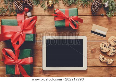 Christmas online shopping background. Tablet screen with copy space top view on wood, credit card and present boxes. Electronic devices, internet commerce on winter holidays concept
