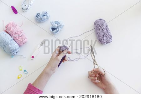 close up of a woman creating with wool hand made bootees for a baby boy