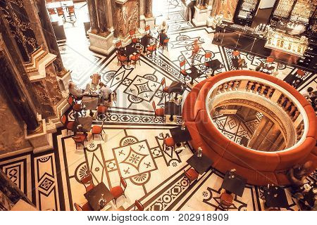 VIENNA, AUSTRIA - JUNE 10, 2016: Patterns on walls and floor inside ancient bar of Kunsthistorisches Museum with relaxing and drinking visitors on June 10, 2016. Musem was opened in 1891
