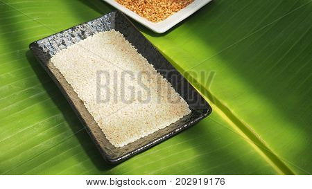White sesame seed in ceramic black plate and roasted in white plate on background banana leaf green color.