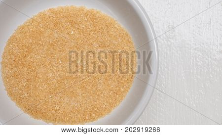 Background brown sugar 5 tablespoons close up detail in white bowl isolate on white wood.