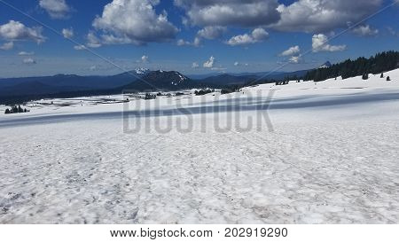 snow capped cascade mountains in crater lake Oregon in mid summer
