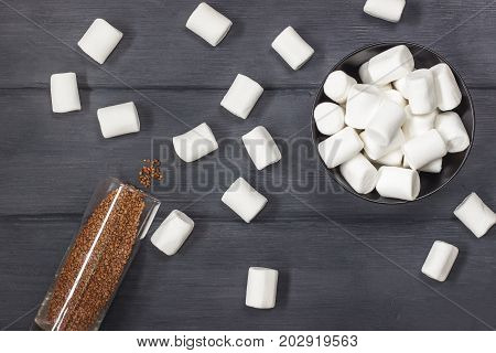 Fluffy white marshmallow in round bowl and instant granulated coffee on black wooden table