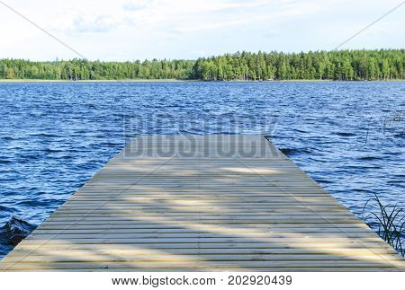 The fishing pier at the lake in rural Finland. Wooden pier at blue water and green forest on sunny day. Wooden jetty bridge with tranquil scene of seascape.