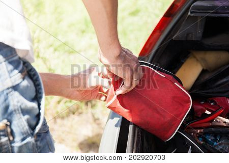 The man is lying first-aid kit in the trunk of the car