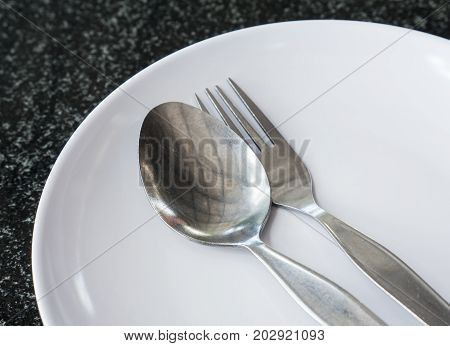 Old sliver spoon and fork on the white ceramic plate of the local restaurant.
