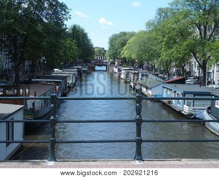Boats in canal gracht ready to cruise and traditional houses in the morning with clear blue sky in 2015 warm sunny summer day, Europe on July.