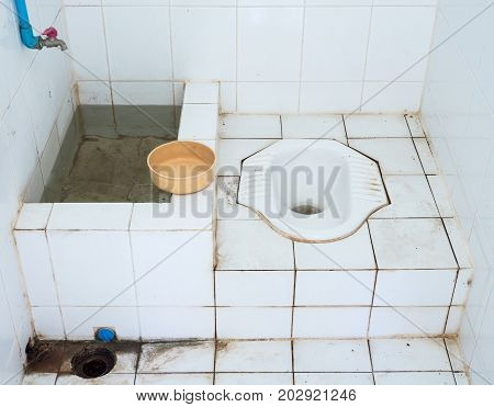 Dirty public toilet with the plastic water bowl in the small templecountryside of Thailand.