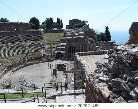 TAORMINA, SICILY ITALY on MAY 2016: Ruins of ancient greek and roman theatre in italian city, seaside mediterranean landscape near ETNA Mount volcano, clear blue sky in warm sunny spring day, Europe.