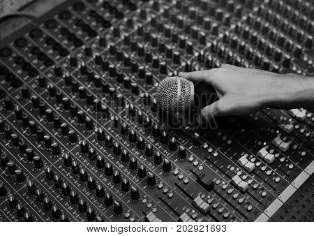 Hand with micro phone on a sound mixer