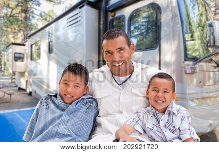 Happy Hispanic Father and Sons In Front of Their Beautiful RV At The Campground.