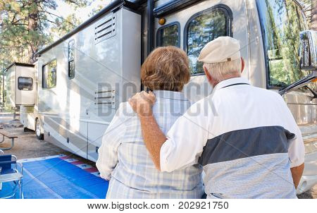 Senior Couple Looking At A Beautiful RV At The Campground.