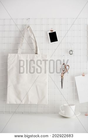 Clean and tidy workspace, white table top and office organizer with lights. White home office room interior, bloggers workplace. Poster and shopping bag mockup.