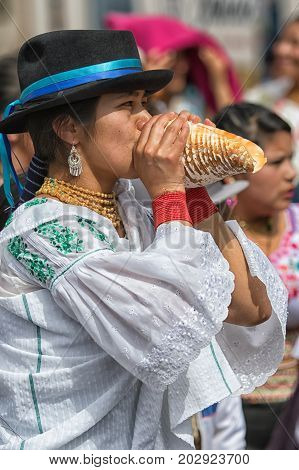 July 1, 2017 Cotacachi, Ecuador: an indigenous Kichwa woman blowing into a conch shell during Inti Raymi celebrations