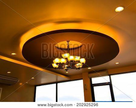 Modern chandelier hanging under ceiling Beautiful modern chandelier in coffee shop or restaurant.