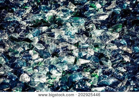 many pieces of broken glass with cracks and splits, a combination of a shade of blue, green, white and gray, close-up, great texture, background,