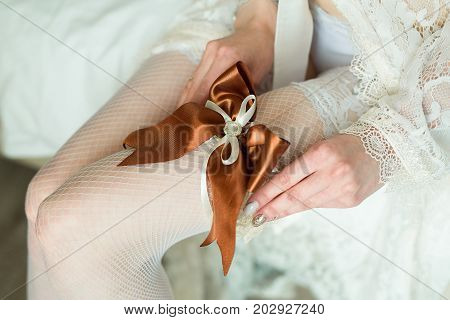 the bride corrects the wedding garter on her leg on the day of the wedding