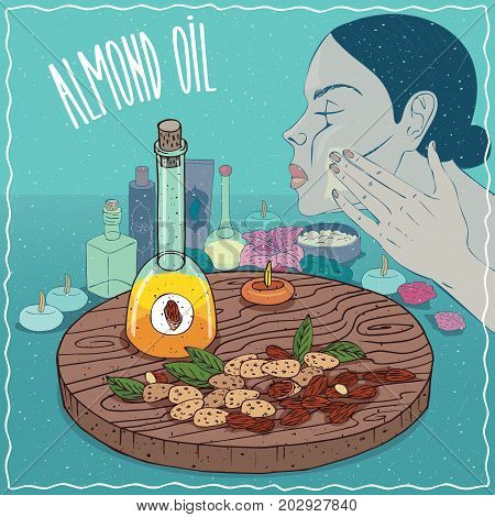 Glass Decanter of Almond oil and sweet kernels of Prunus dulcis plant. Girl applying facial mask on face. Natural vegetable oil used for skin care