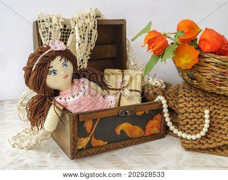 Handmade crochet doll and box on light background.