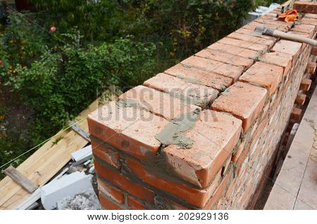 Close up on Bricklaying on house construction brick wall.