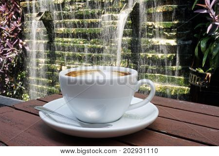 cup of latte coffee in white cup on wooden table with waterfall background.
