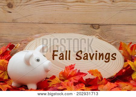 Fall Savings message Some fall leaves with cut wood plaque and an piggy bank on weathered wood with text Fall Savings