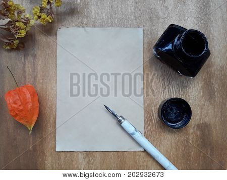 Dry autumn flowers and a blank old sheet of paper with a dip pen and an inkwell on a worn wooden background (view from the top or flat lay)