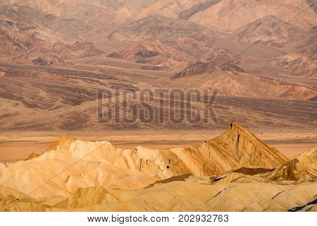 Zabriskie Point and hills bathed in early morning golden light in Death Valley National Park in California
