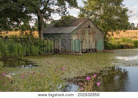 An old metal corrugated derelict boat shed a standing in the corner of a pool showing signs of neglect