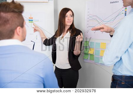 Confident businesswoman communicating with male colleague while pointing at chart in office