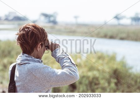 Tourist Watching Wildlife By Binocular On Chobe River, Namibia Botswana Border, Africa. Chobe Nation