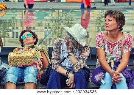CLUJ-NAPOCA ROMANIA - SEPTEMBER 2 2017: Two middle age and a senior women recover on a bench after sightseeing tour.Vintage effect applied.