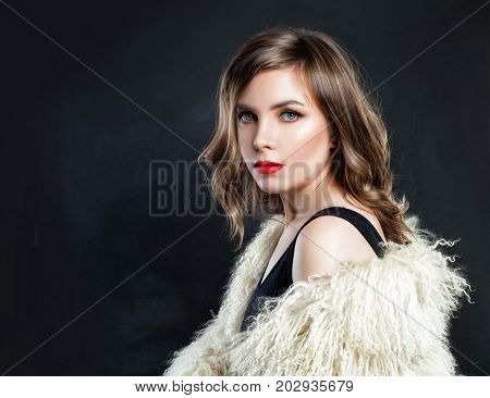 Beautiful Young Lady in Fur Coat Posing on Dark Background. Perfect Fashion Model Woman with Makeup and Bob Hairstyle