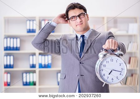 Businessman with alarm clock in the office