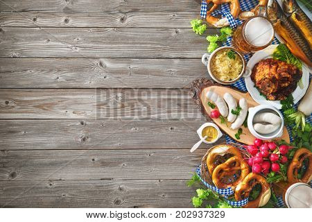Oktoberfest beer, pretzels and various Bavarian specialties on wooden background