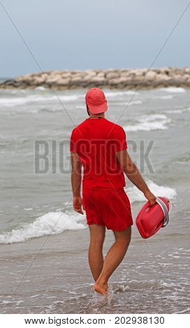 Lifeguard With Red Uniform Checks The Bathers With The Rugged Se