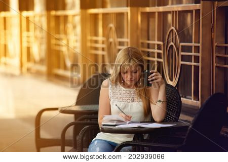 Pretty Blonde Girl Copywriter Sitting On Cafe Terrace With Coffee. Woman Freelancer Writing Outdoors