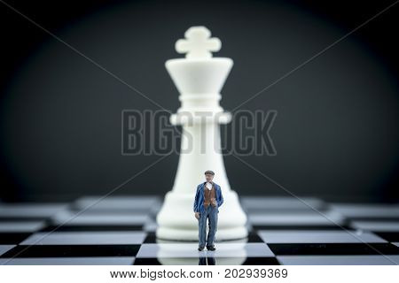 Miniature figure of a man in front of chess piece, conceptual image