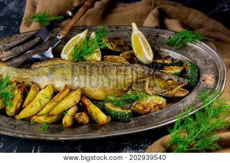 baked pike-perch with potatoes, zucchini and lemon