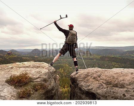 Tourist With Medicine Crutch Above Head Achieved Mountain Peak. Hiker With Broken Leg