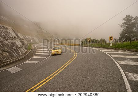 July 11 2017 Tolima Colombia: a vehicle is descending in thick fog on a high altitude road in the Andes
