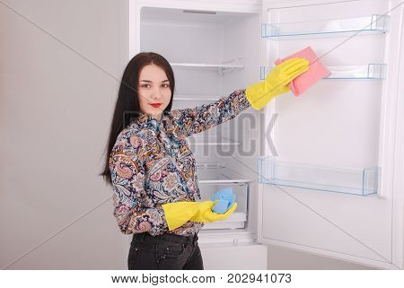 Young girl cleaning empty fridge with a sponge. Beautiful young girl near the fridge.